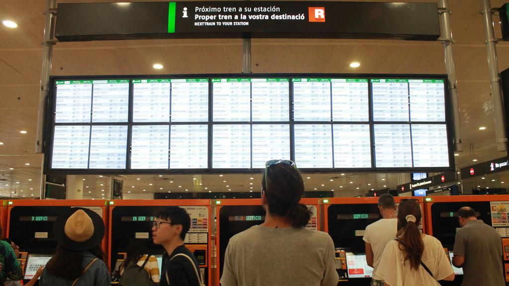 Un grup d'usuaris de Rodalies, majoritàriament turistes, observa les pantalles d'informació de l'estació de Sants durant la vaga del 12 de juny de 2016. (Horitzontal)