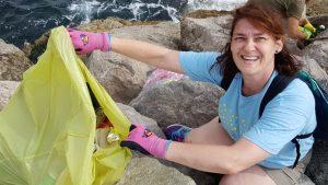 Una voluntària carrega una bossa plena de plàstic