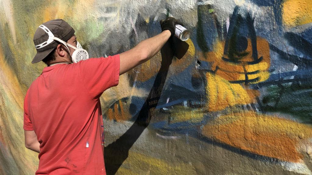 L'artista Juanjo Surace fent el mural per No Borders