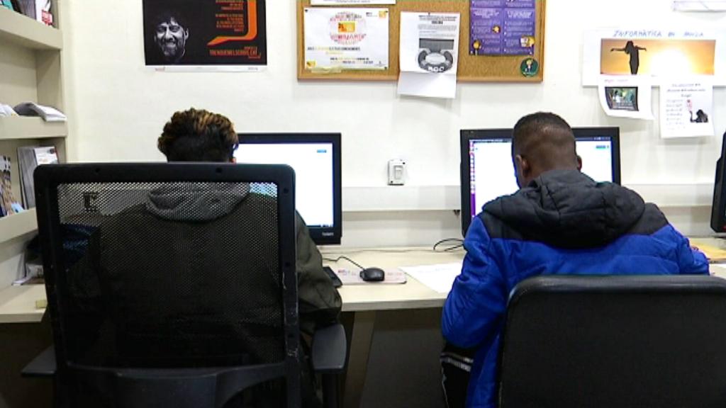 Joves estrangers a l'aula d'informàtica de la Fundació Comtal.