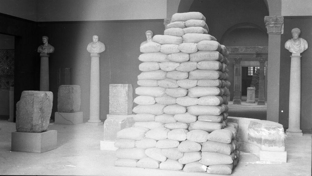 Interior del Museu d'Arqueologia de Catalunya amb els sacs de terra protegint l'escultura de la sala d'Inscripcions commemoratives. Foto Ramírez Sagarra (atrib) (MAC.AHF)