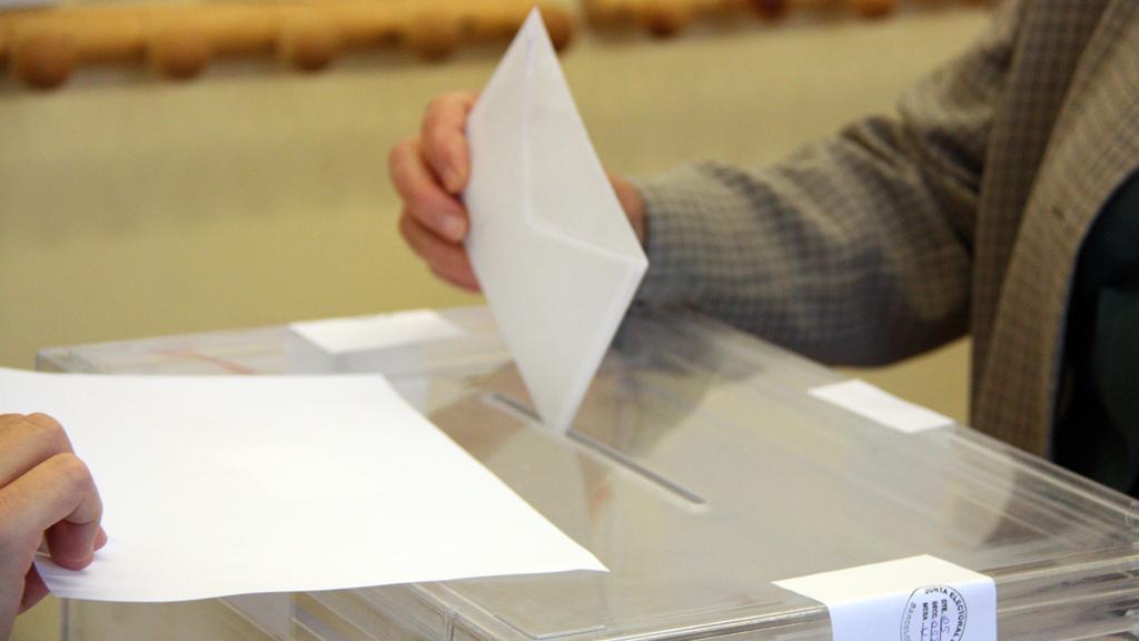 Votant dipositant el sobre a l'urna