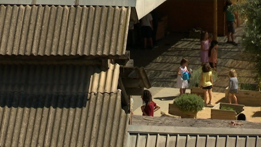 Nens juguen al costat d'una teulada d'uralita