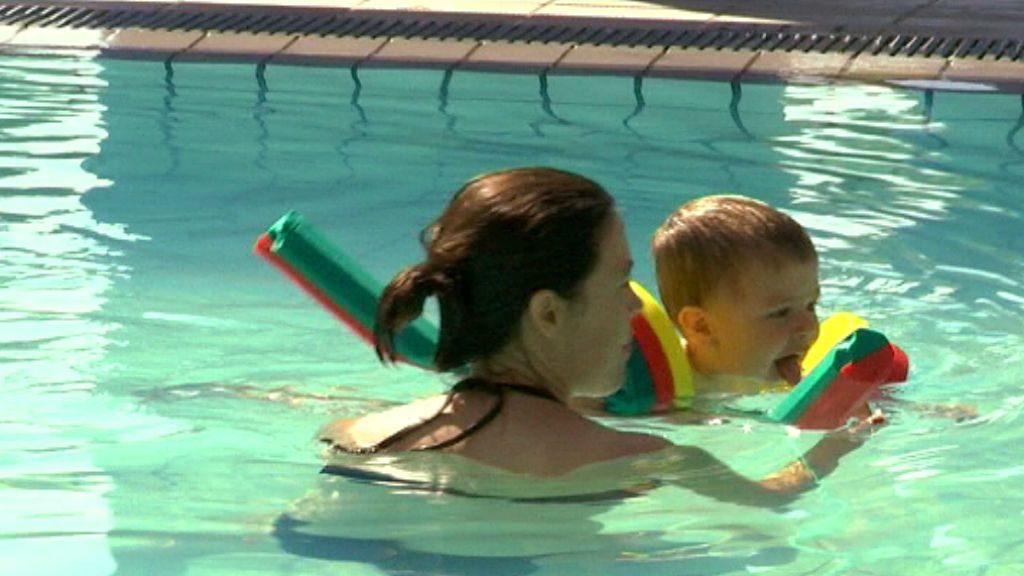 Mare i fill banyant-se en una piscina a l'estiu
