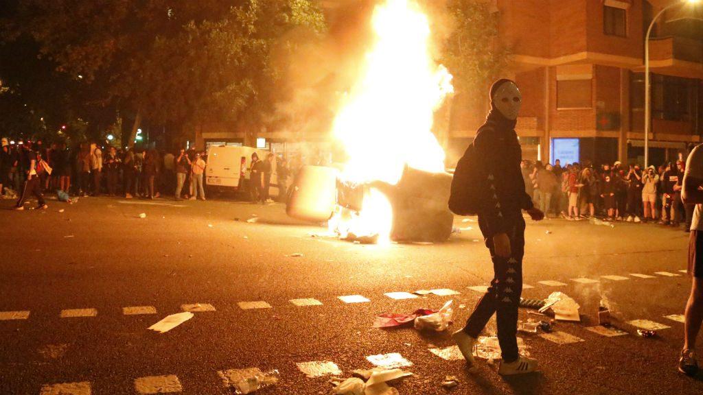 Manifestant davant d'un contenidor en flames