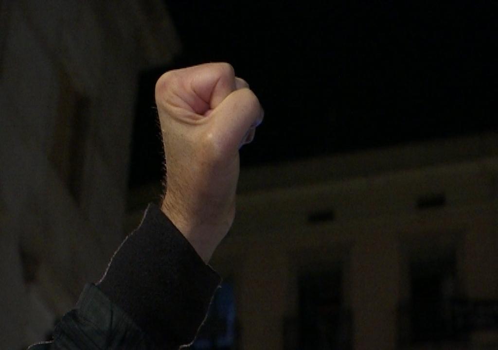 Una persona alça el puny a la plaça Sant Jaume