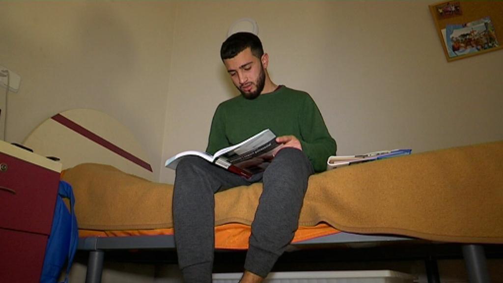 L'Abdel fulleja llibres de text a la seva habitació.