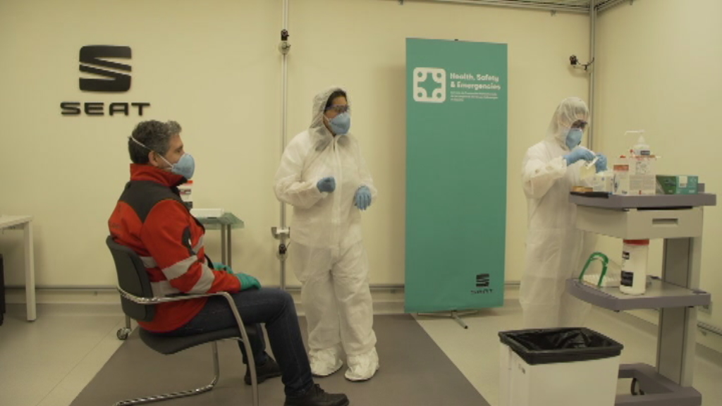 Dos professionals sanitaris fent la prova PCR a un empleat de la Seat