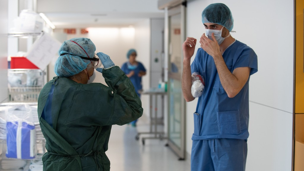 Conversa entre dos sanitaris al passadís d'un hospital