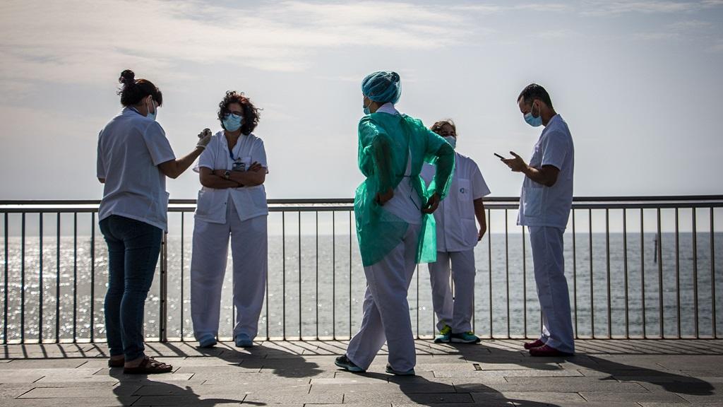Un grup de treballadors sanitaris de l'Hospital del Mar conversen al passeig marítim durant la fase 0 de la desescalada del confinament pel coronavirus