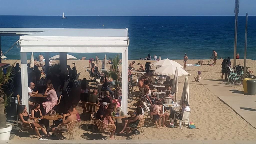 Taules sobre la sorra de la platja a un xiringuito del Bogatell