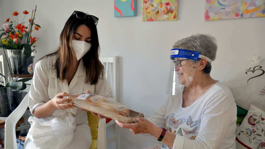 Una voluntària d'Avismón lliure una coca de Sant Joan a una persona gran
