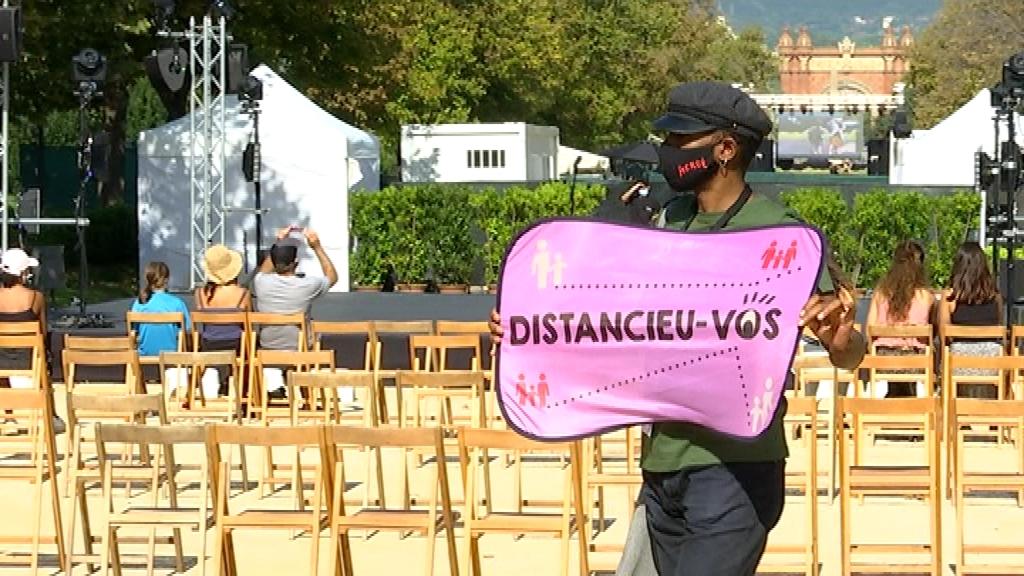 Un informador amb un cartell de distància a la Mercè 2020