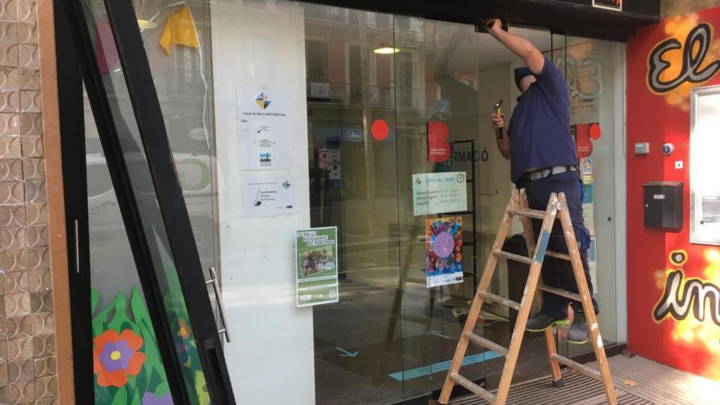 Un operari repara la porta del Casal de Barri del Poblenou