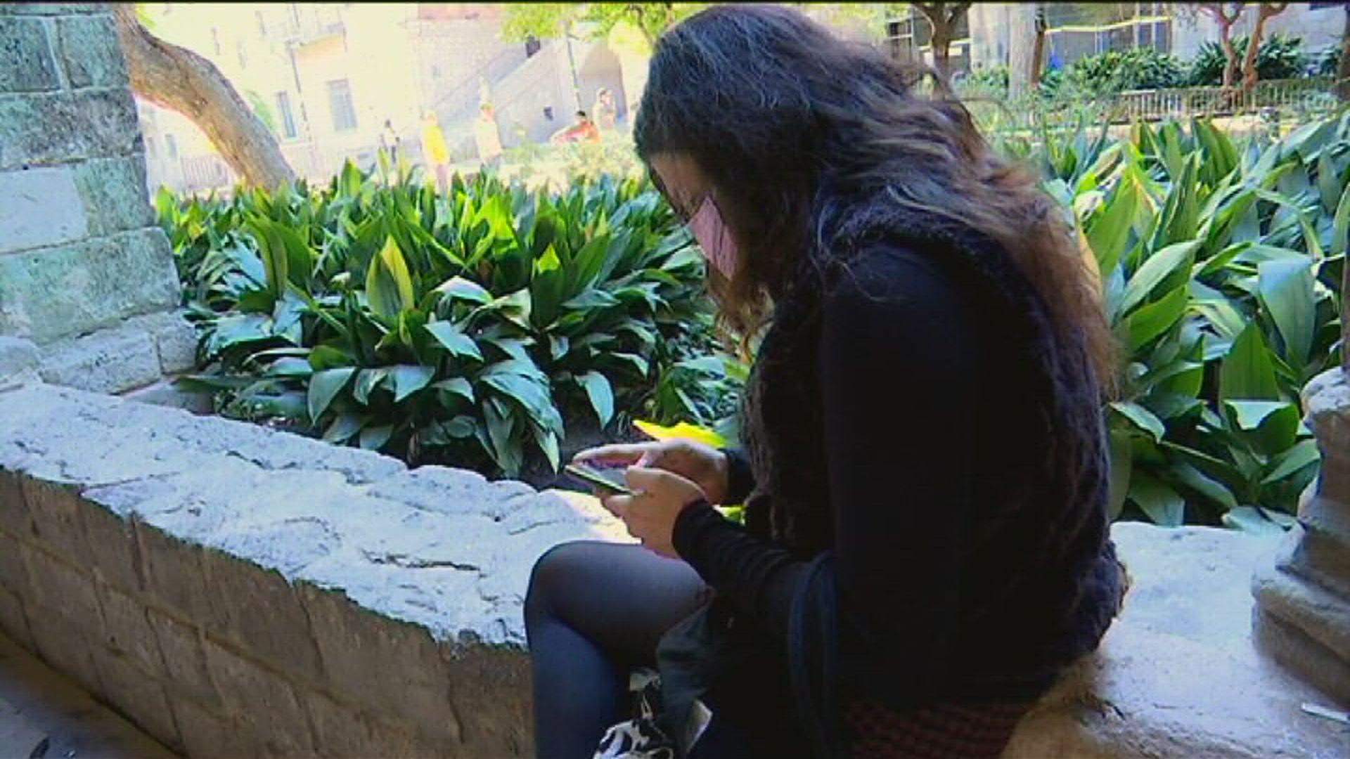 Edén Provecho consulta el seu telèfon mòbil abans de conversar amb betevé