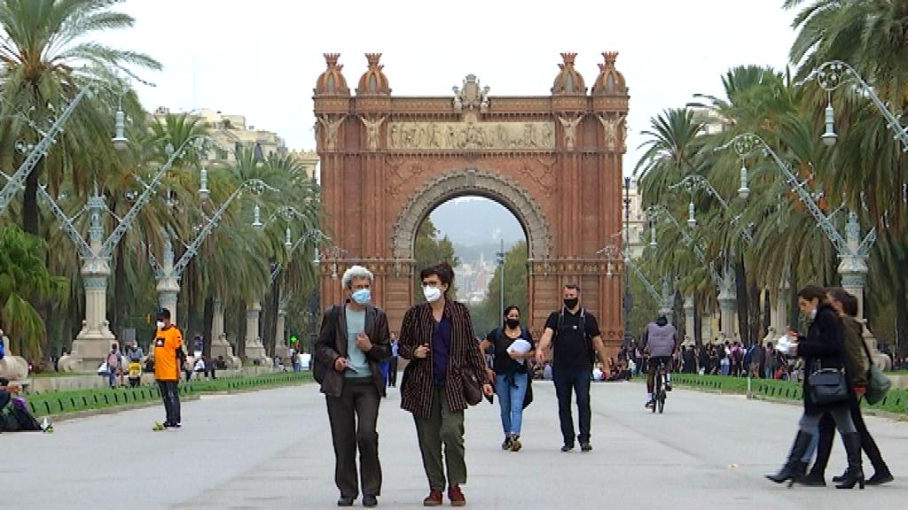 Gent passejant amb l'Arc de Triomf de fons