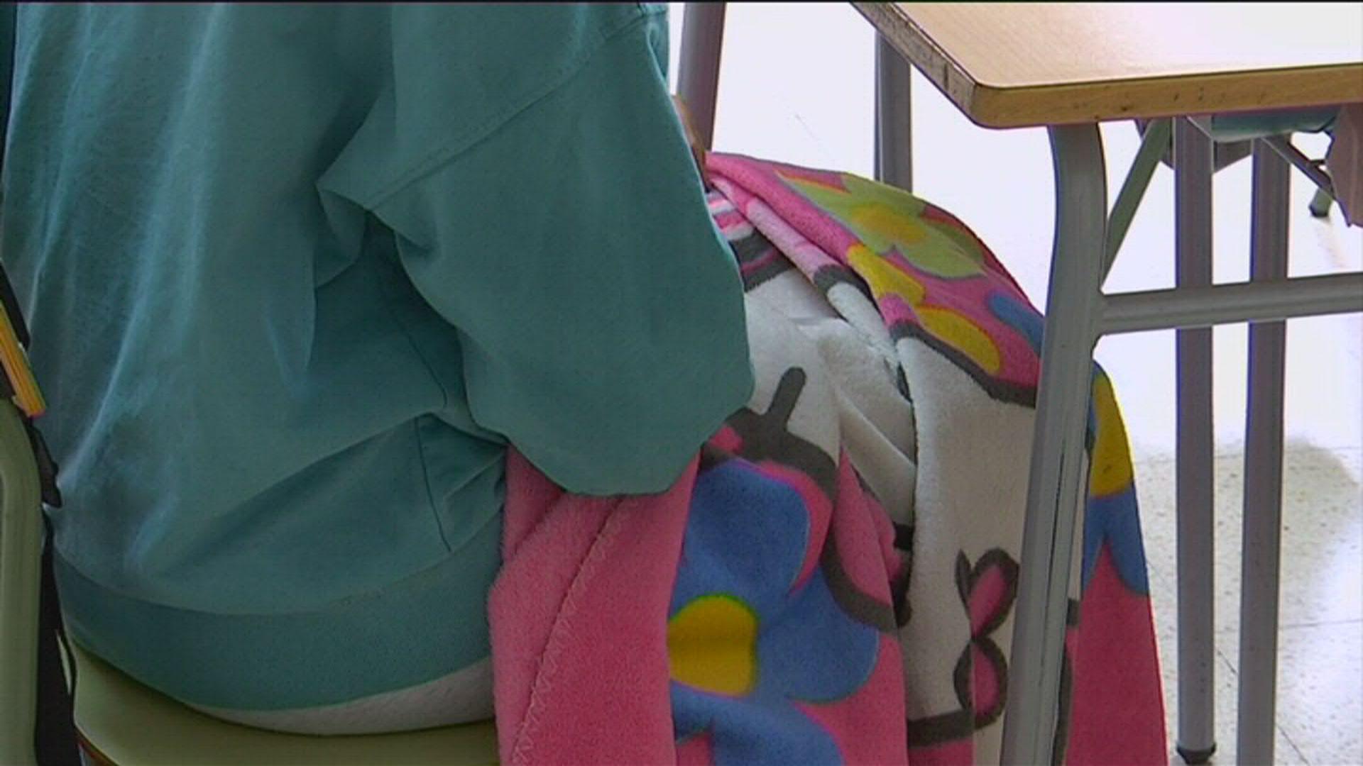 Alumne ESO a l'Institut amb manta a la classe