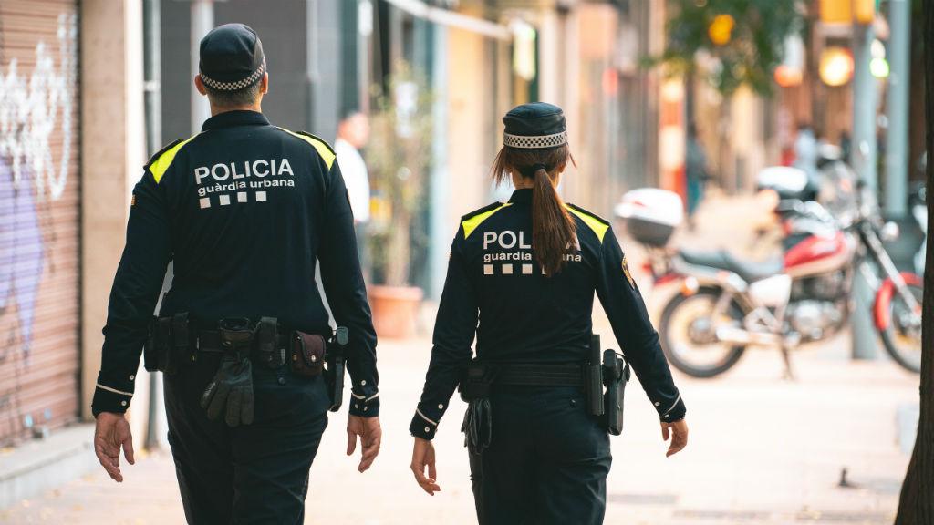 Una parella d'agent de la Guàrdia Urbana patrullen pel carrer
