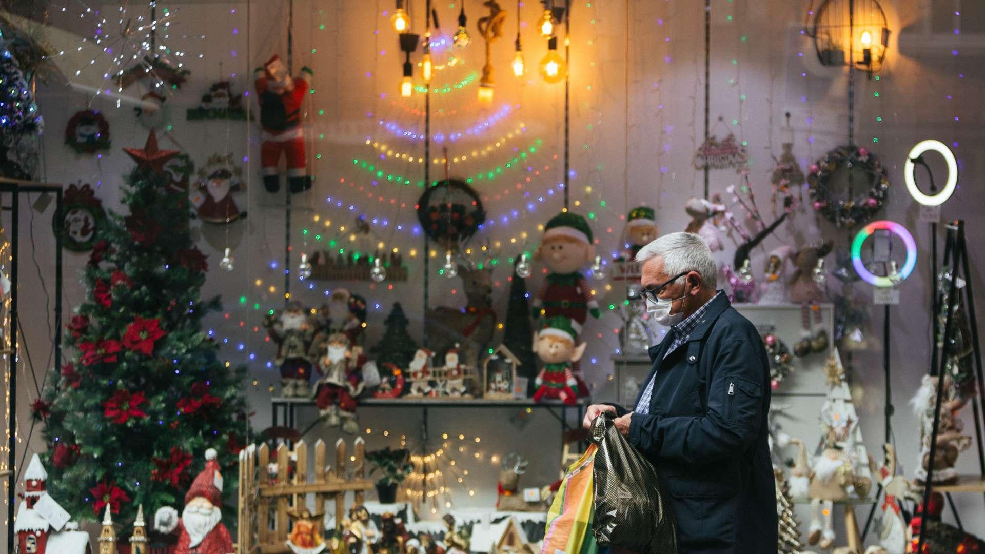 Una persona gran passa davant d'un aparador ple d'objectes de Nadal
