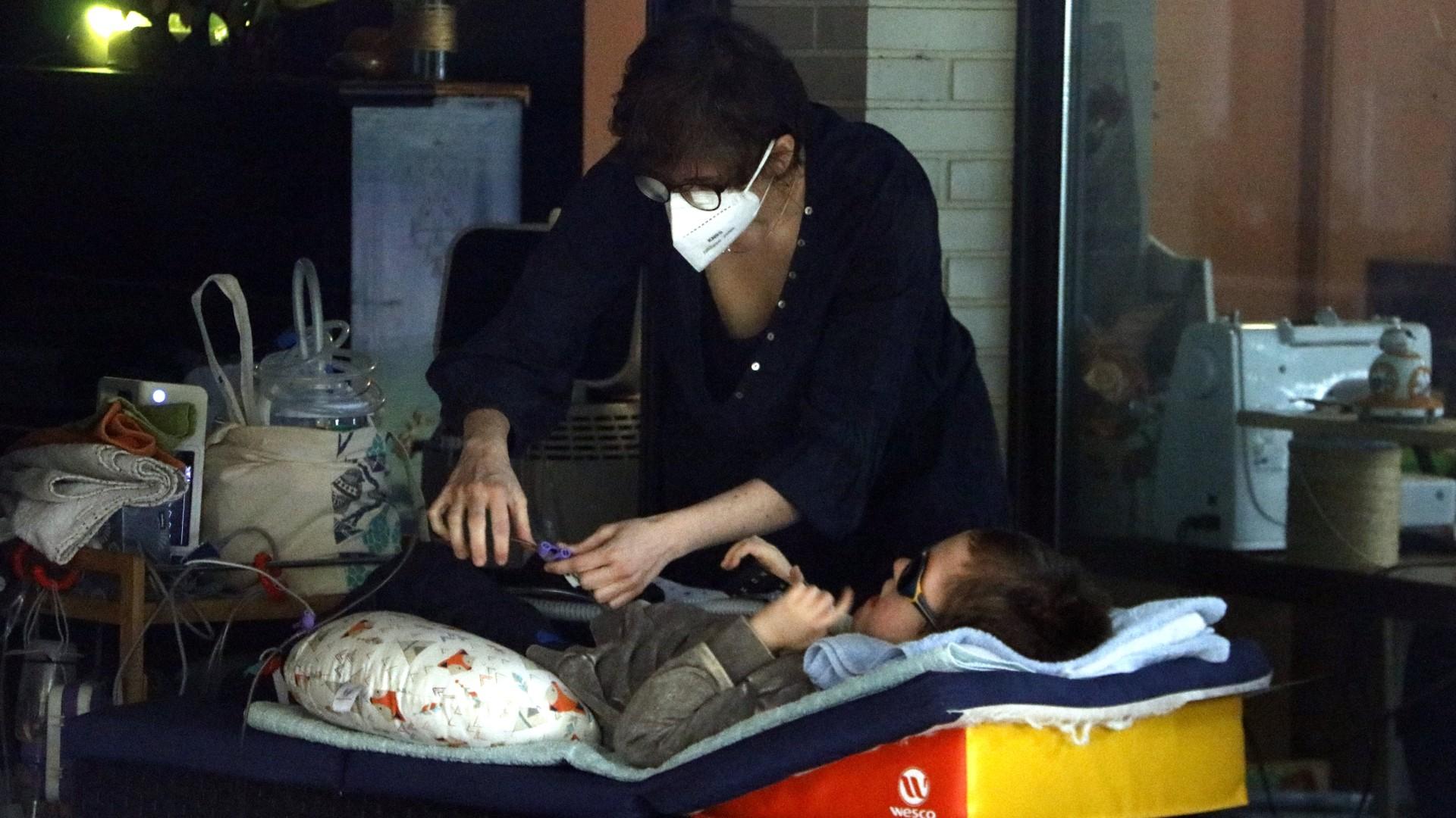 Pla mitjà del Lluc, un nen amb una malaltia minoritària, i la seva mare, Glòria Llumà, al jardí de casa