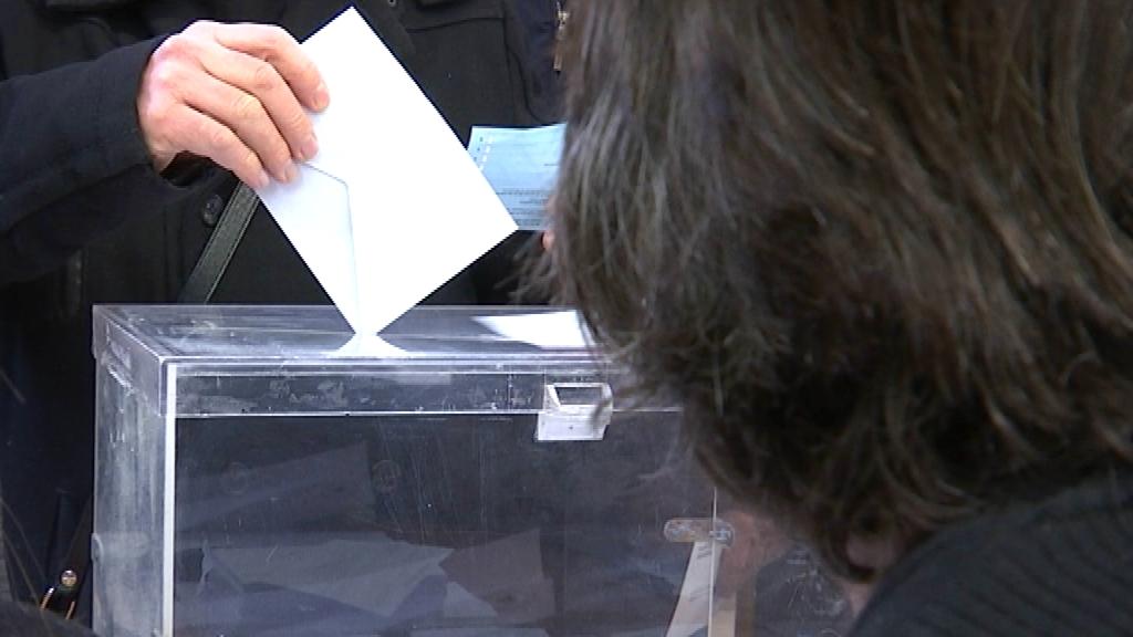 Votant dipositant el vot en una urna