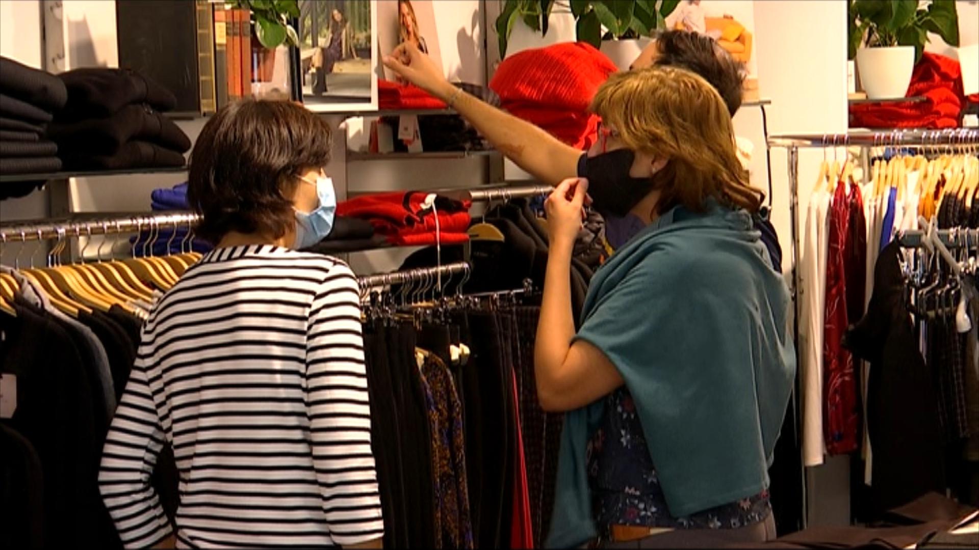 clients en una botiga de roba