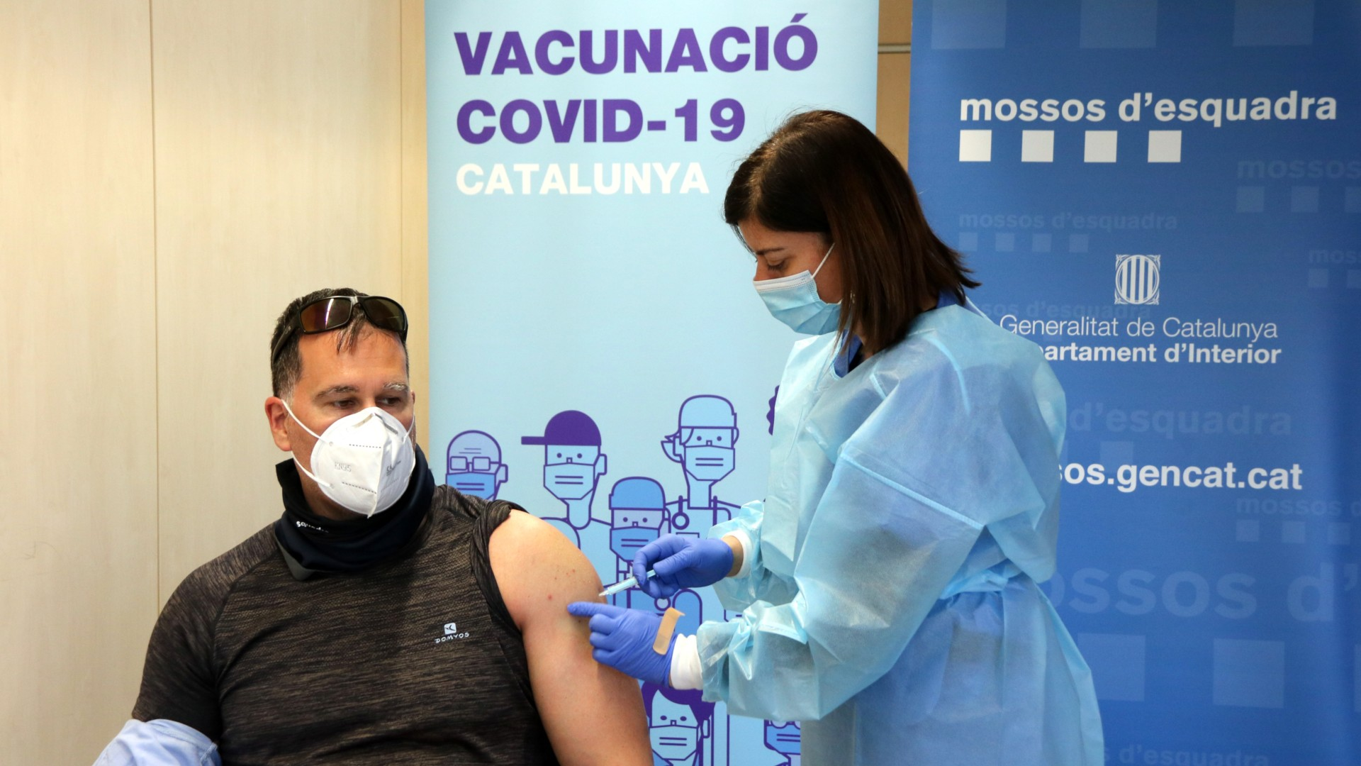 Pla mitjà d'una infermera administrant la primera dosi de la vacuna d'AstraZeneca a un policia