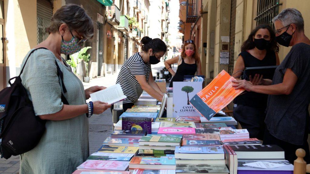 compradors mirant llibres a parada Casa Anita Sant Jordi d'estiu