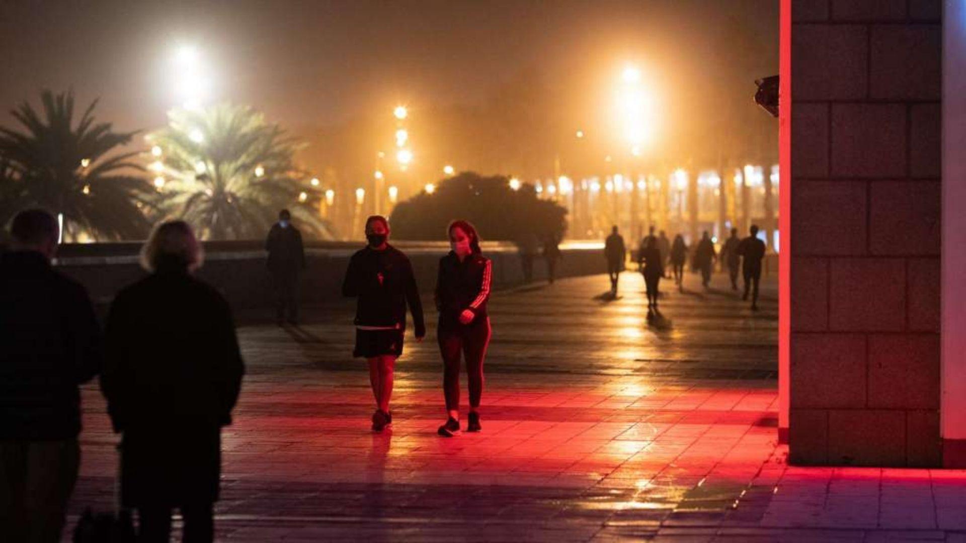 gent passejant de nit a la barceloneta toc de queda