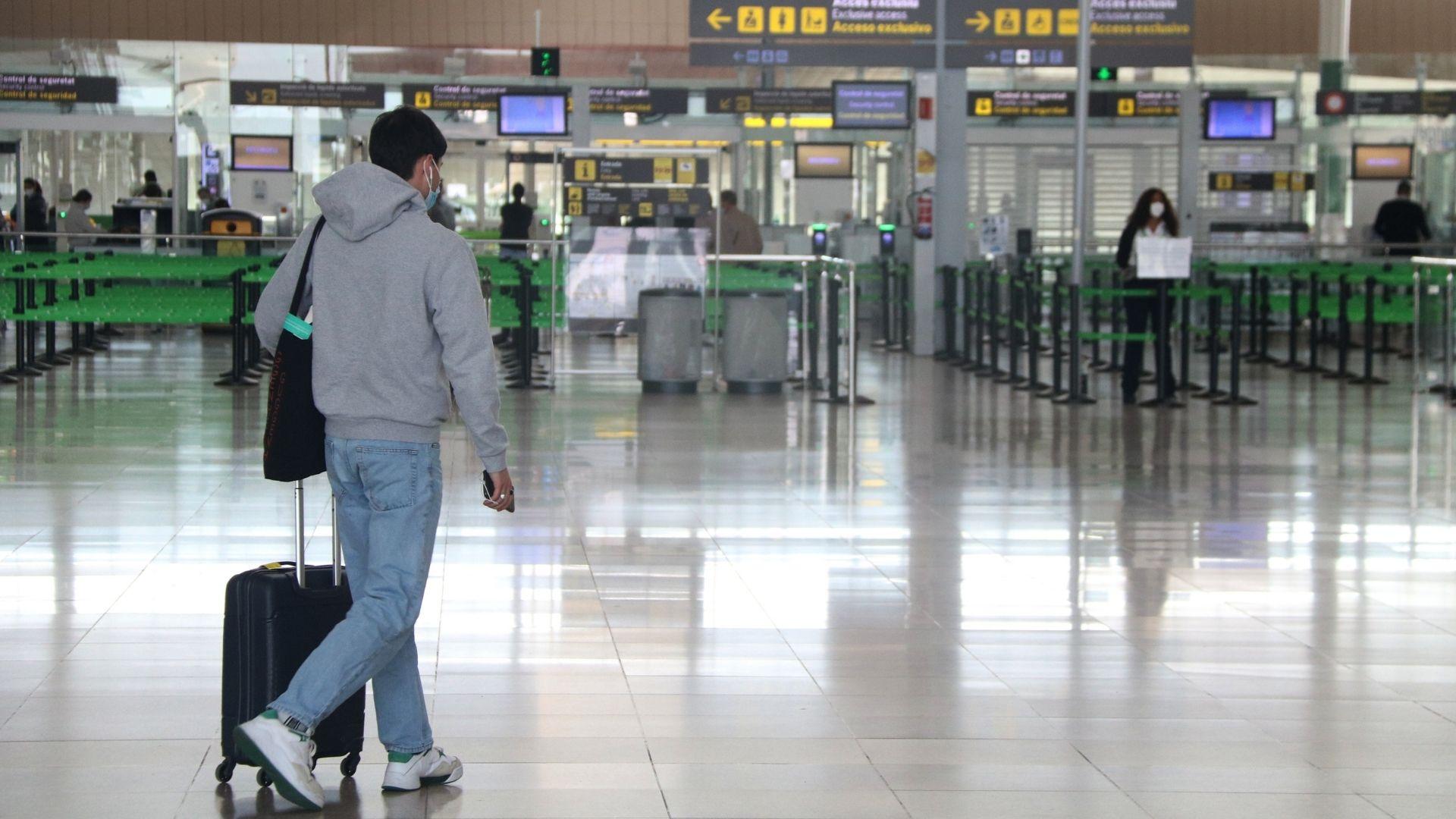 Pla obert d'un passatger a la zona d'arribades de la T1 de l'aeroport del Prat