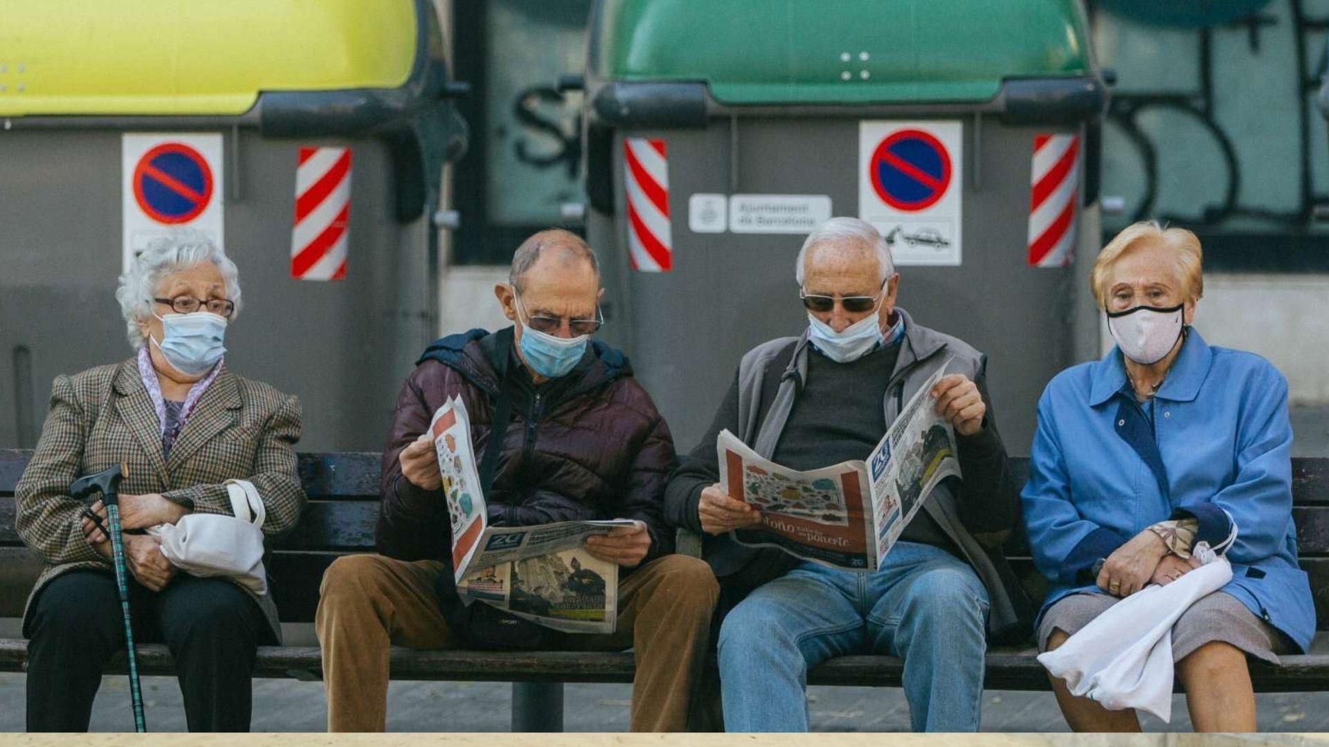 Persones amb mascareta assegudes en un banc.