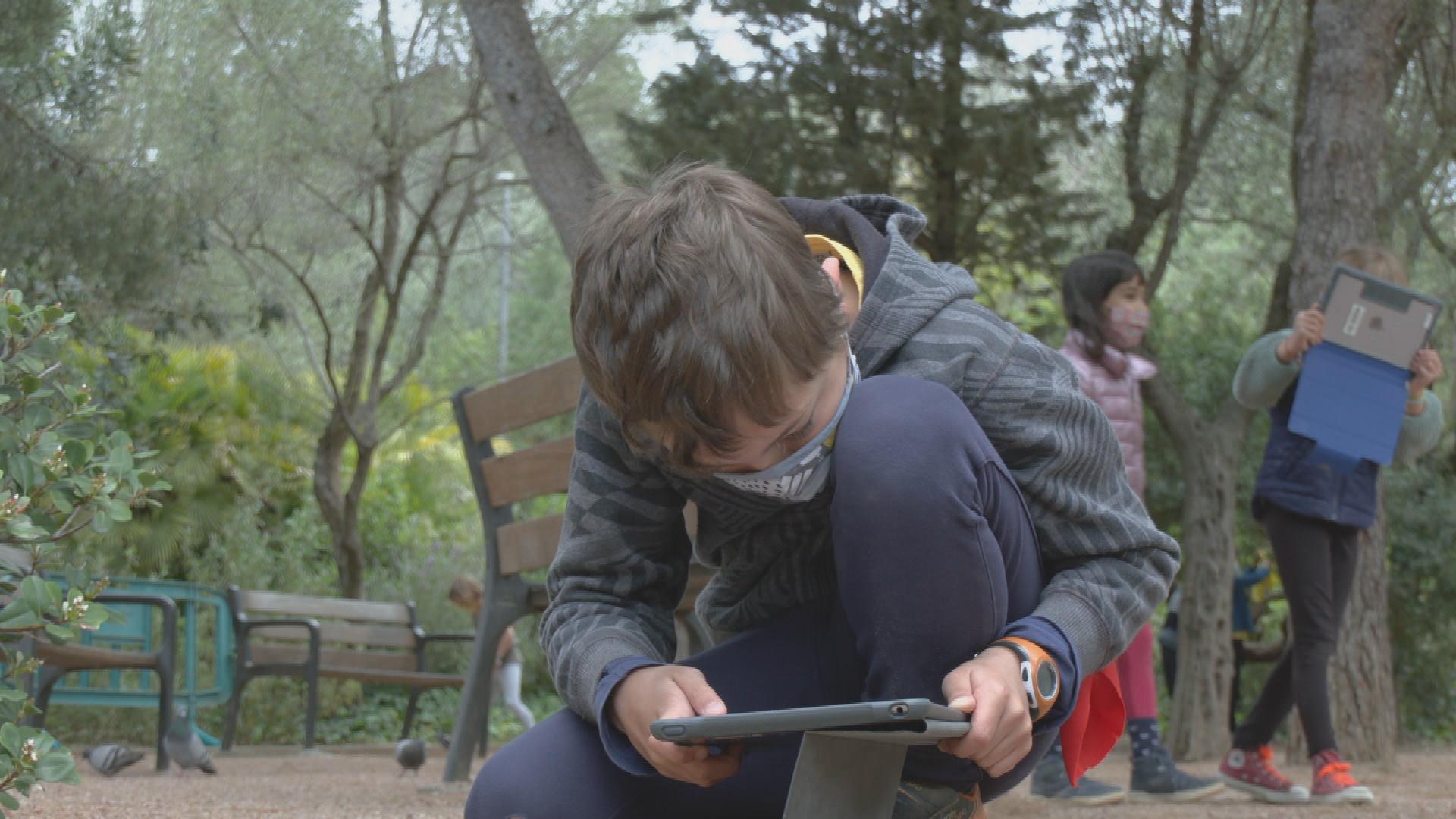 nen grava amb tauleta al Parc Güell